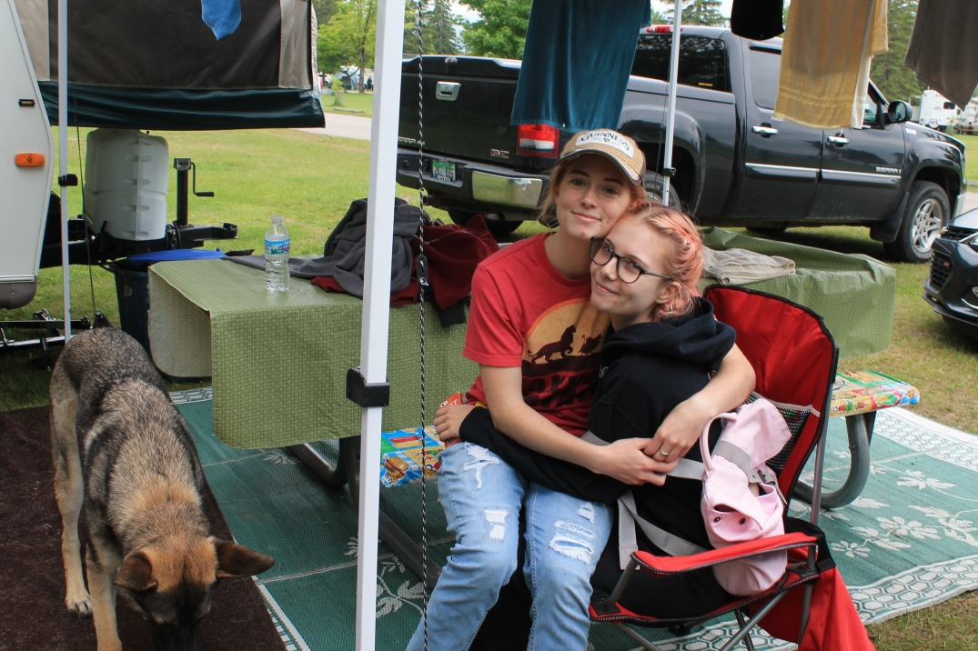 Two girls hug each other, smiling. There is a large dog beside them.