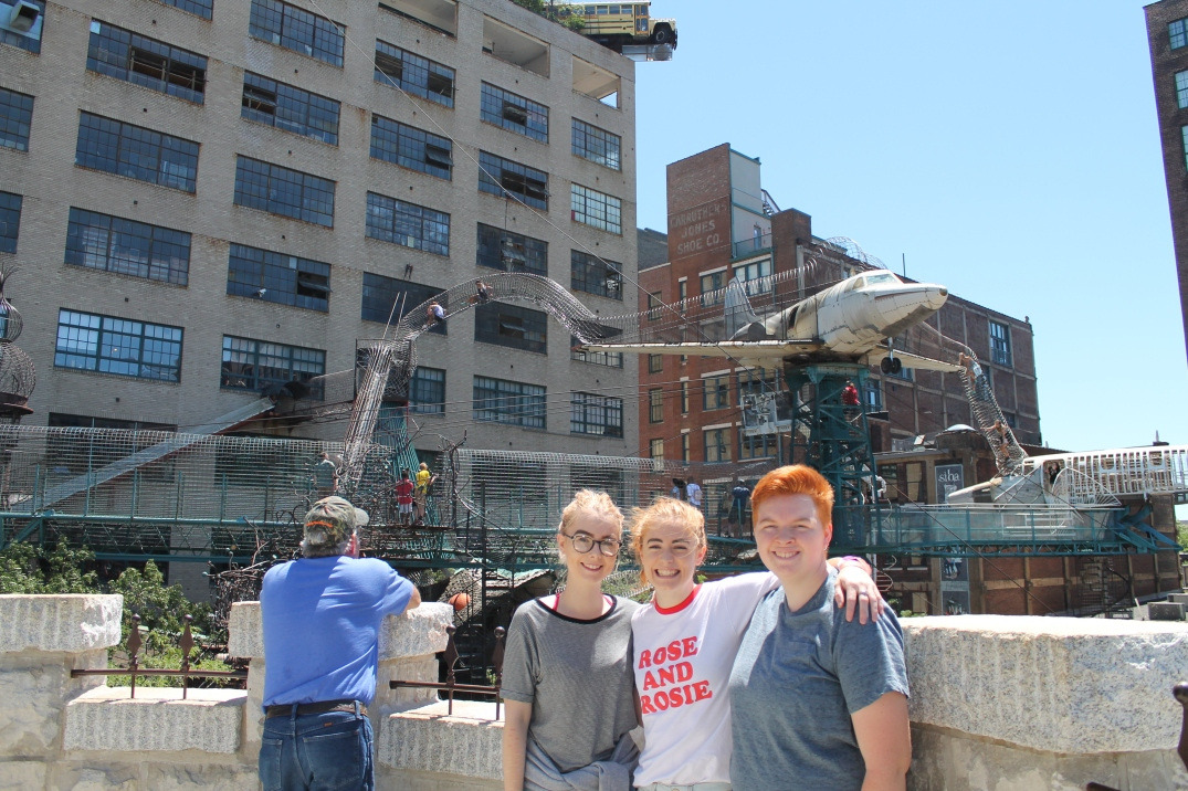 Three smiling girls pose outside of a tall building. In front of the building are metallic tunnels several stories tall, with people crawling through them.