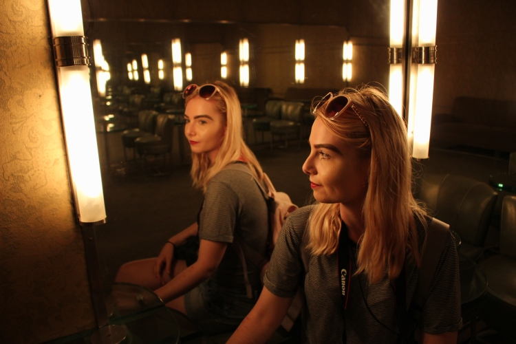 A woman sits in front of a mirror with dim lighting. Her profile is reflected in the mirror behind her.