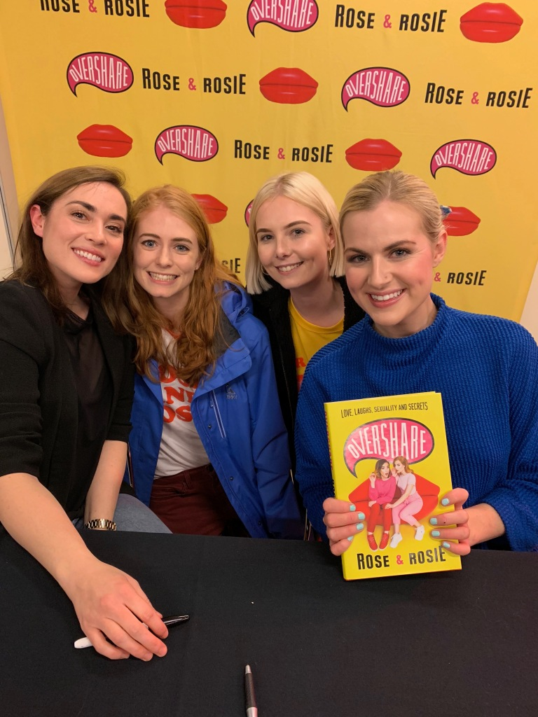 Jas and Jess pose with a photo with Rose and Rosie. All four women are smiling. Jess' cheek is close to Rose' cheek. Rosie is holding the book titled, Overshare.