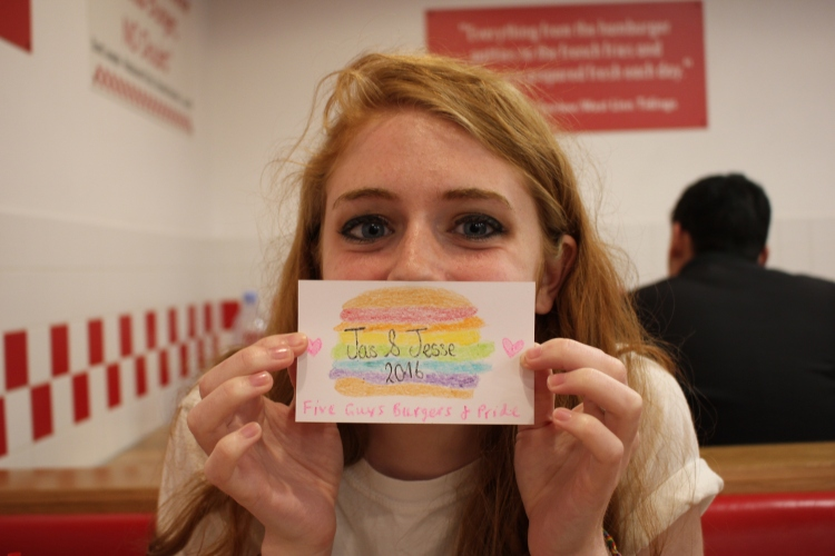 Jesse holds up a crayon drawing in a Five Guys. The drawing is a cheeseburger with rainbow fixings. The drawing states, Jas and Jesse, 2016. Five Guys Burgers and Pride.