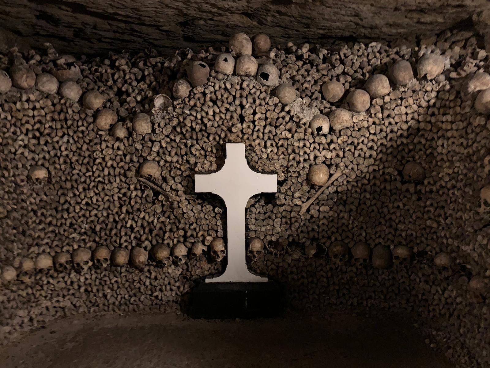Hundreds of femur bones line a cave wall, with some rows of skulls stacked between femurs. A cross is at the center of the bone stack.