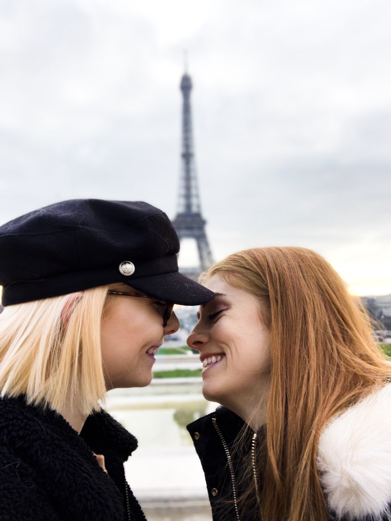The writer and her girlfriend smile at each other before kissing. The Eiffel Tower is distance in the background.
