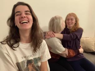 Dasha laughs. Jess and Jas have their arms around each other in the background.