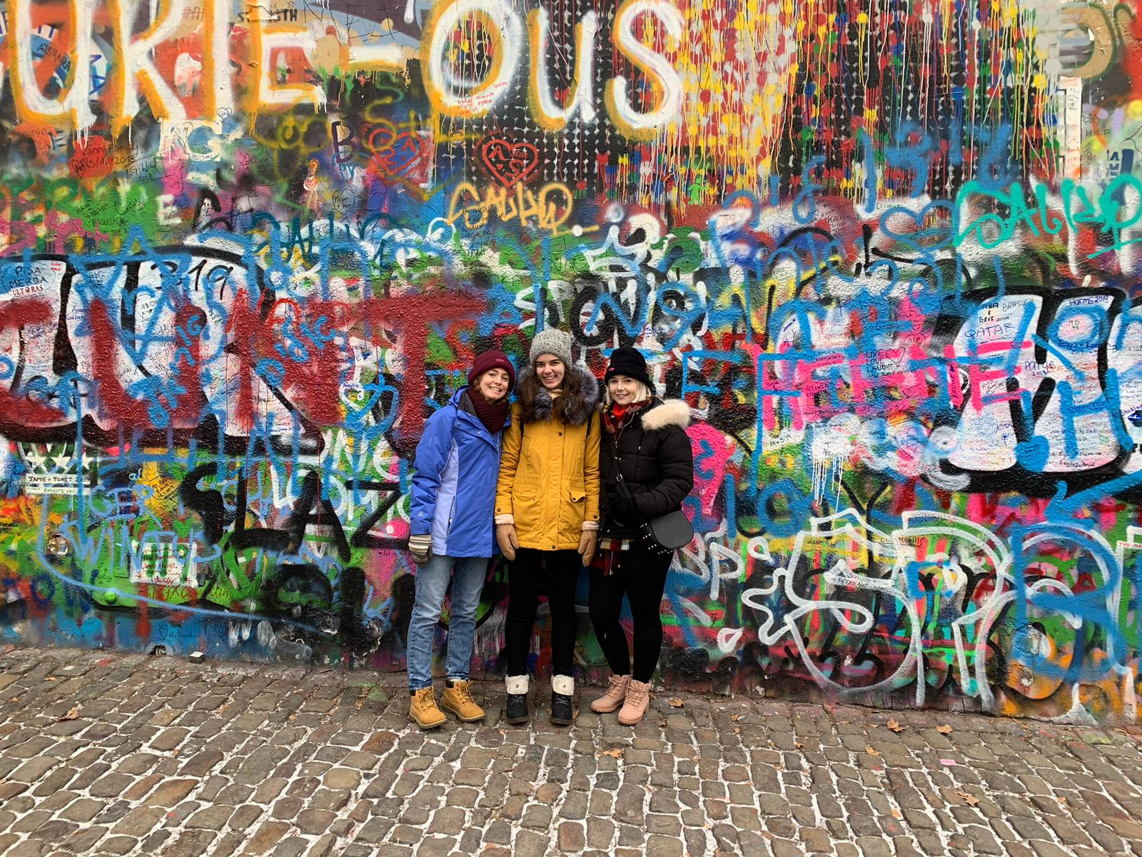 Jess, Dasha, and Jas, stand in front of a wall covered in overlapping graffiti. Many of the visible words are not in English.