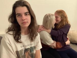 Dasha looks annoyed. Jess and Jas kiss in the background with their arms around each other.
