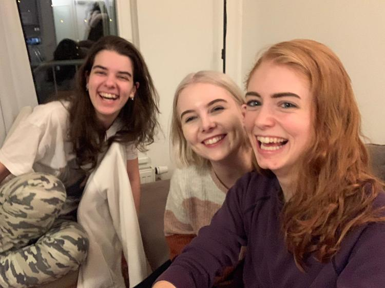 All three girls look at the camera while laughing.