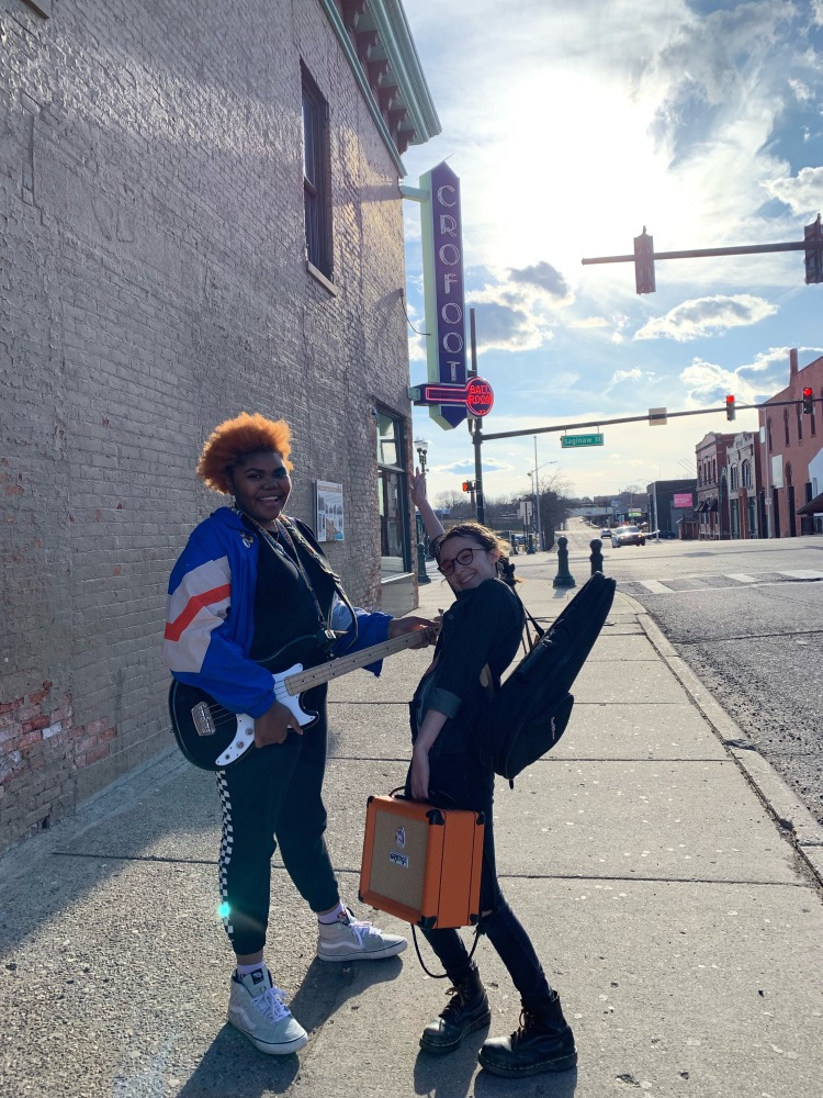 The two bandmates pose in the street holding a guitar and amp in their hands.