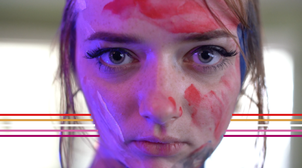 A still from Sandbagger shows a young woman staring past the camera. There is red and white paint on her face.