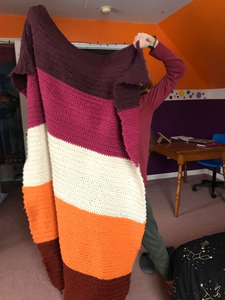 A person holds a crocheted blanket. The blanket is as long as the person holding it. The blanket has 5 equal colors from top to bottom as follows. Purple, pink, white, light orange, dark orange.