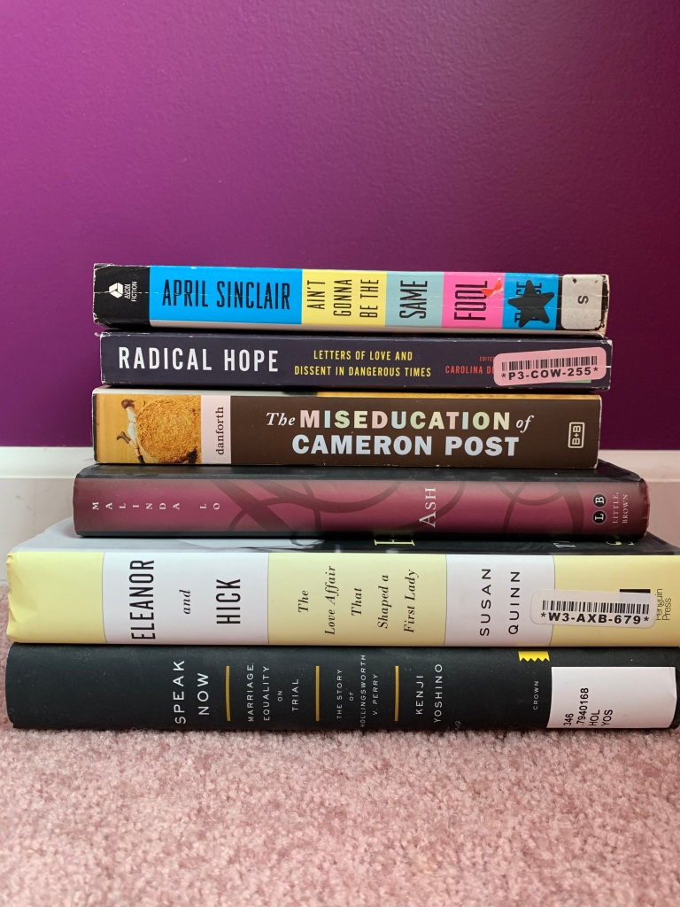 A stack of books includes 6 titles as follows. Speak now, marriage equality on trial by Kenji Yoshino. Eleanor and Hick, the love affair that shaped a first lady, by susan quinn. Ash by Malinda Low. The Miseducation of cameron Post by Danforth. Radical Hope, letters of love and dissent in dangerous times. Editor not visible. Ain't gonna be the same fool twice by April Sinclair.