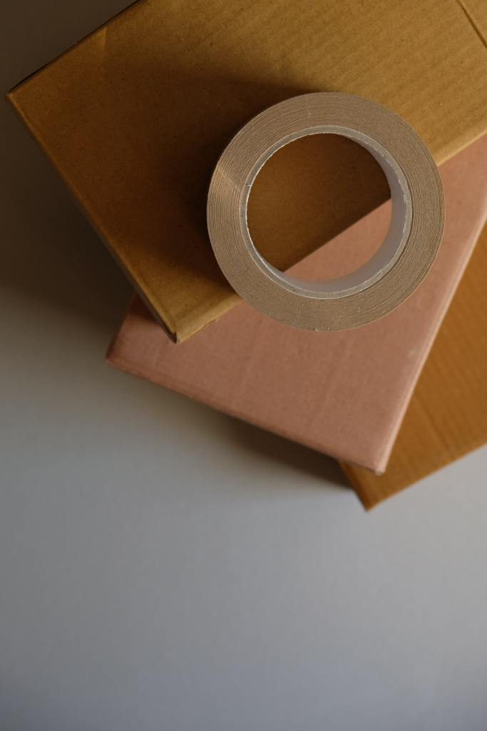 A roll of tape rest on top of a package ready for shipping.