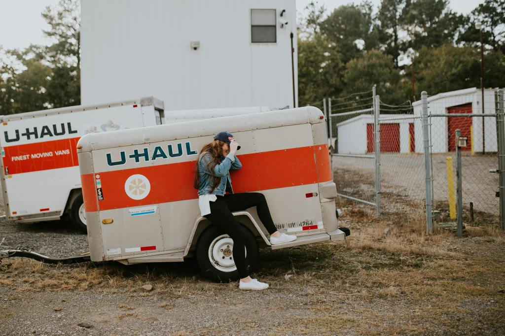 A girl sits on the tire of a U Haul trailer.