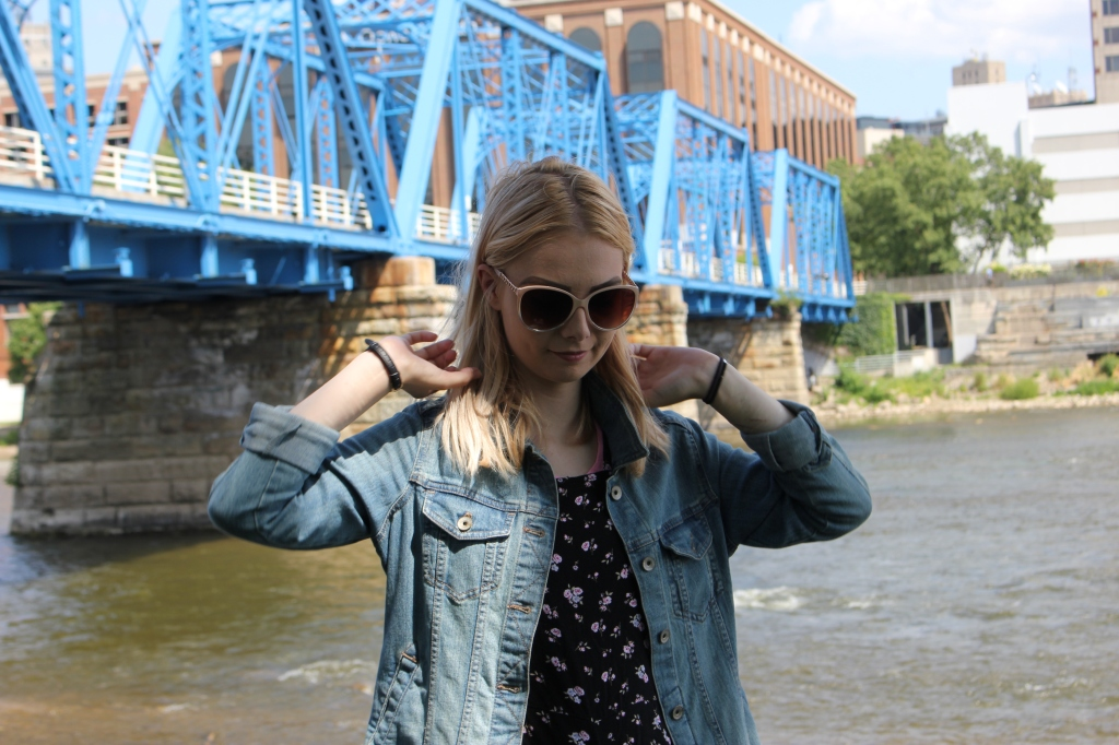 A young blonde woman stands in front of a river and iconic blue walking bridge.