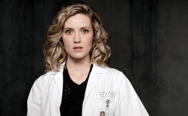 Delphine Cormier, a blonde woman wearing a lab coat, stares into the camera.