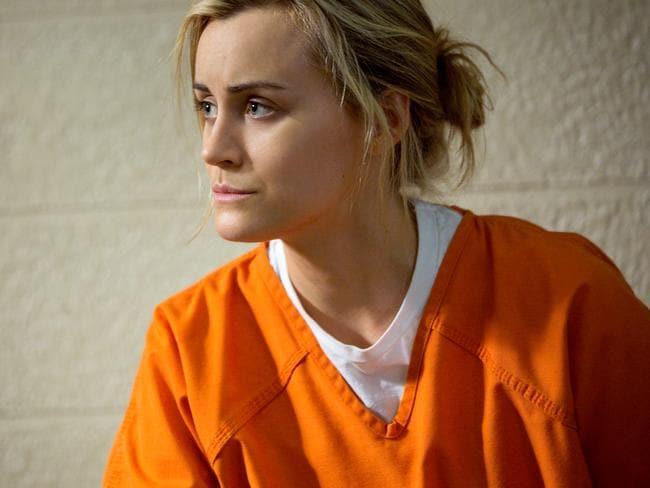 Piper Chapman, a blonde woman, wears an orange prison uniform.