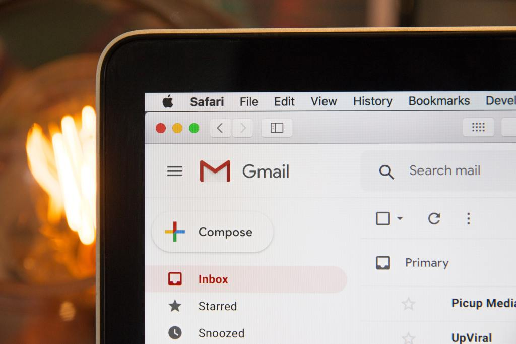 The web browser, Safari, is open on a laptop, displaying a Gmail inbox.