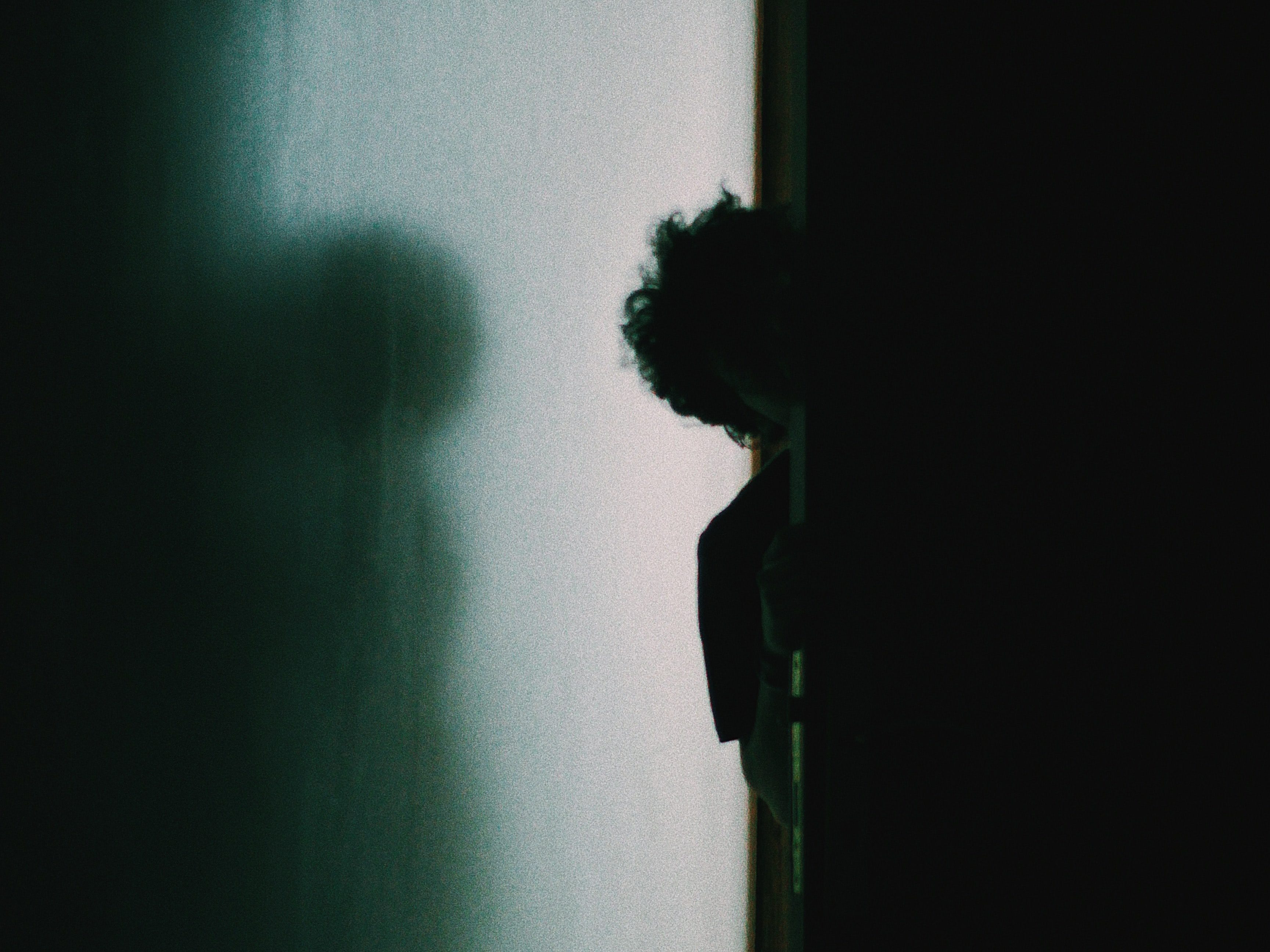 A silhouette of a person peers around a corner.