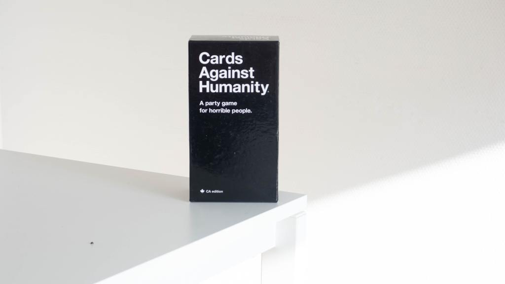 Decorative. A pack of Cards Against Humanity stands on a table.
