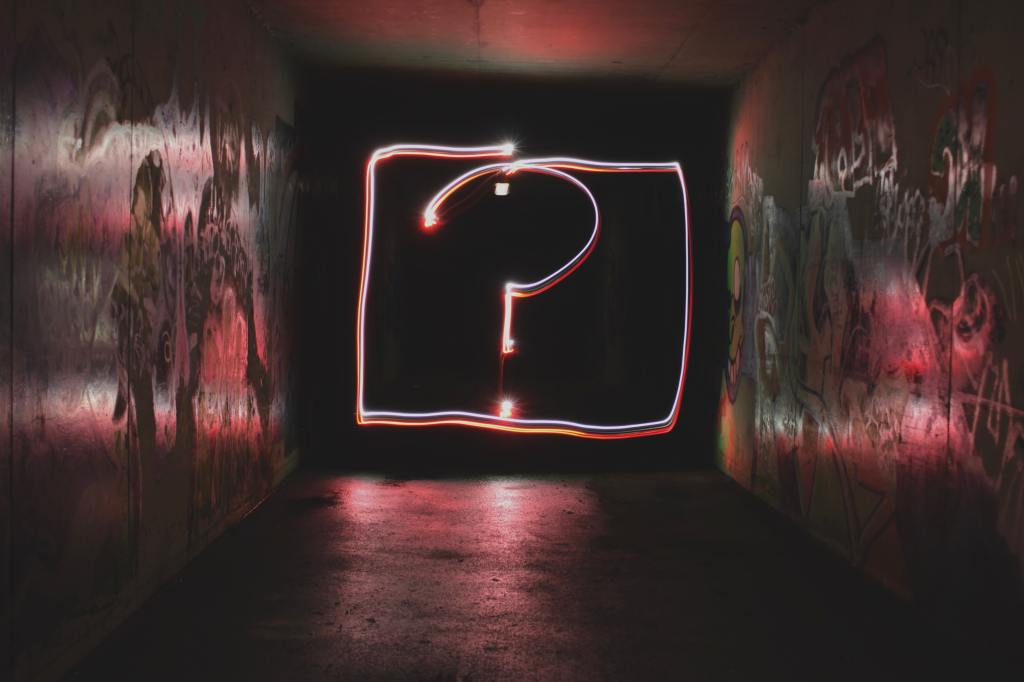 A hand drawn light is in the shape of a question mark with a box around it. The question mark is at the end of a dark tunnel with graffiti around the walls.