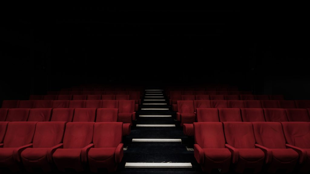 Decorative. A cinema includes rows of empty, red theatre chairs.